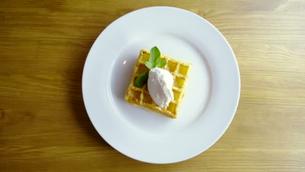 Sweet breakfast. Top view of viennese waffles with ice cream and mint on a white plate. 4K
