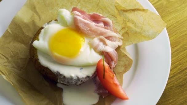 Angol reggeli. Közelkép lövés buggyantott tojást és szalonnát, pirítóssal, friss zöldségek. 4k