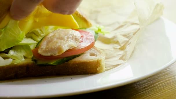Csirke szendvics. Két darab kenyér sajttal, hús, paradicsom, uborka, fejes saláta, mártás fokhagymával közöttük. 4k