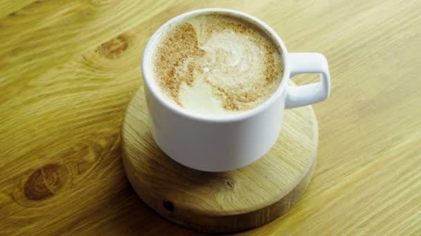 Cappuccino. Közelről lövés olasz csésze kávé forró tej és fahéj por tetején. 4k