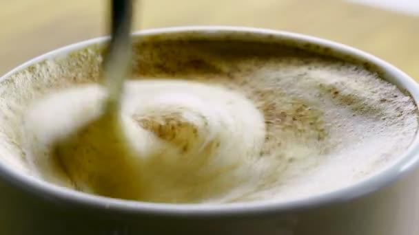 Reggeli. Közeli lövés cappuccino csésze kávét is keverik kanállal. 4k