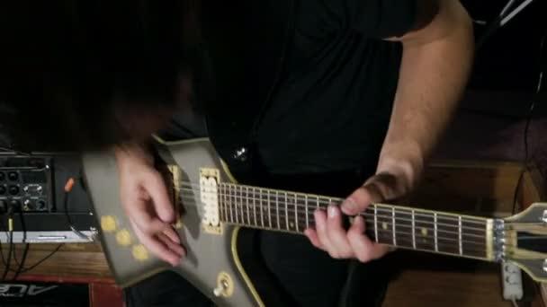 Szólógitáros a fém sávban. Gitárjátékos teljesítő a színpadon. Videoklip a punk, heavy metal vagy rock csoportban. Lassított. Hd