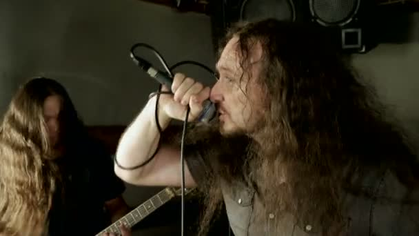 Musical metal band. Man singing a song into microphone, having performance with rock band in studio. 4K