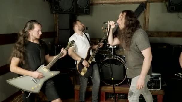 Hudební metalová kapela. Skupina hudebníků hrající rockovou hudbu na jevišti. 4k
