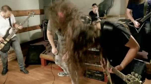 Szólógitáros a fém sávban. Gitárjátékos teljesítő a színpadon. Videoklip a punk, heavy metal vagy rock csoportban. 4k