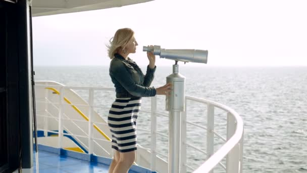 Mature adult blonde woman standing on deck of cruise ship and looking through tourist binoculars at seascape. Slow motion. HD