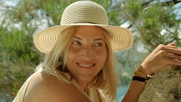 Krásná šťastná žena oblečená v plavkách a slaměném klobouku a vydávala se na pláž proti klidnému moři. Zpomaleně. Hd