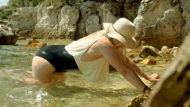 attraktive fröhlich lächelnde blonde Frau in Badeanzug und Strohhut posiert am Strand und genießt ihre Reise, ihren Urlaub und das Meer. Zeitlupe. hd