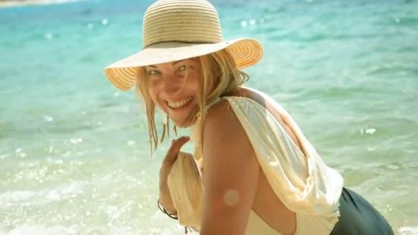 schöne glückliche Frau in Badeanzug und Strohhut, die am Strand gegen die ruhige See posiert. Zeitlupe. hd