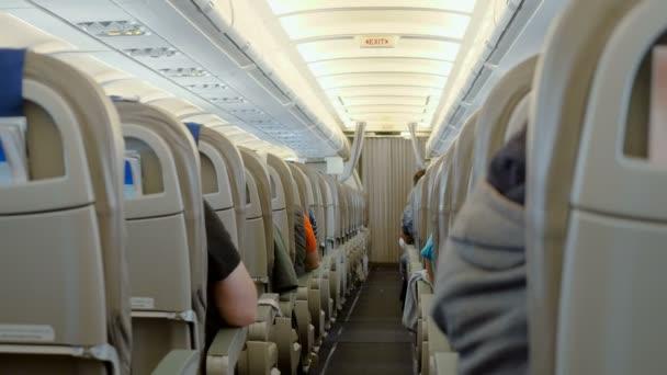 Vnitřek letadla. Řady sedadel v letadle s cestujícími na palubě. 4k