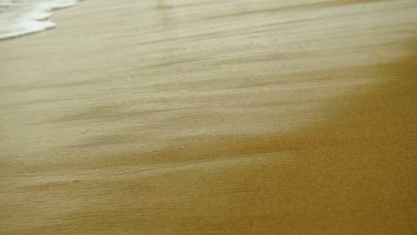 Záběr vlny, která se rozbíjí na písčitém pobřeží Středozemního moře. Řecko. 4k
