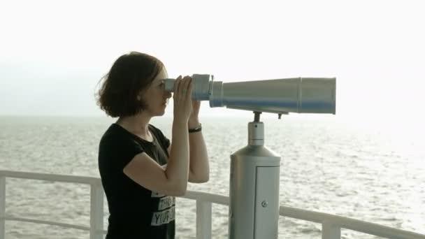 Nő sötét hajú keres a turista távcsövet a Földközi-tengeren. 4k