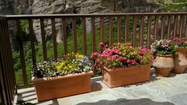 Öt agyagos virágcserép virágzó növényekből áll a verandán, kilátással a hegyekre. Görögországban. 4k