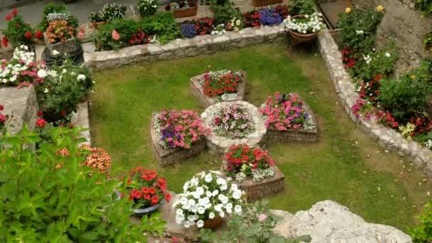 Květinové záhony ve tvaru kříže v zahradě ortodoxních klášterů Meteora na řeckých skalách. Řecko. 4k