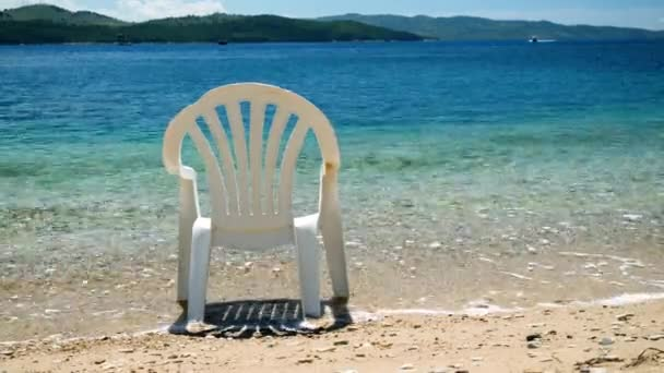 An empty plastic chair left on shore of the Mediterranean sea. Greece. 4K