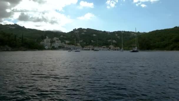 Plachetnice plující ve Středozemním moři. Skalnatý výběžek Korfu. Krajina středomořského pobřeží v Řecku. 4k