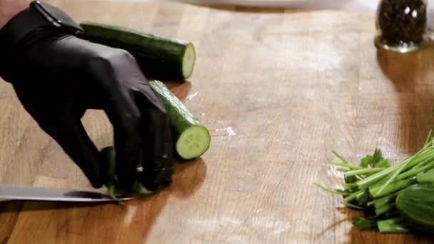 Detailní záběr mužských rukou krájejících okurku na sekačce v módní kuchyni. 4K