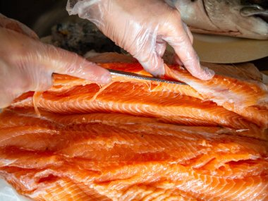 Closeup of workers hands cutting fish with knife at table