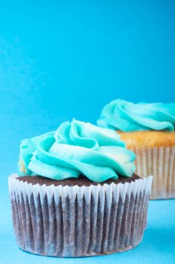 Christmas chocolate and vanilla cupcakes on blue background. Selective focus. Party concept.
