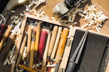 Many various cutters and tools for wood carving in wooden box with wooden shavings. Flat lay