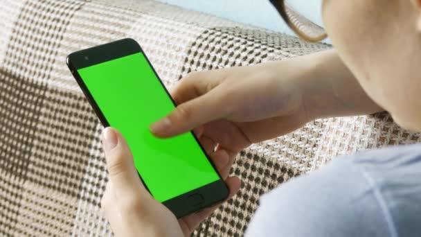 Obrázek ženských rukou přidržoval a používá bílý mobilní telefon s prázdnou obrazovkou. Moderní mobilní telefon. Chroma klíč. Zavři to. Svislé.