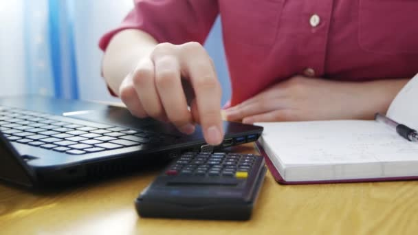 Close up calculator on table, female hands typing on laptop, student writing research or graduate work, doing homework, woman checking budget, calculate money.  Concept working at home, freelance.
