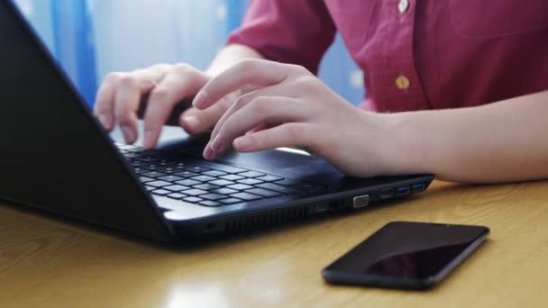 Egy nő gépel a laptop billentyűzetén, és üzenetet kapott a telefonon. Női kezek bezárása laptop billentyűzeten. Fogalom dolgozik otthon, szabadúszó.