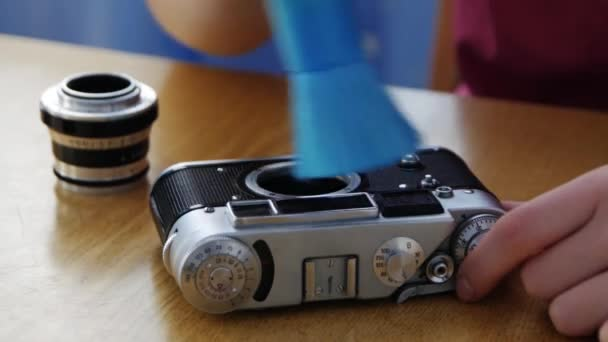 Photographer changing lens on vintage film photography camera in home.
