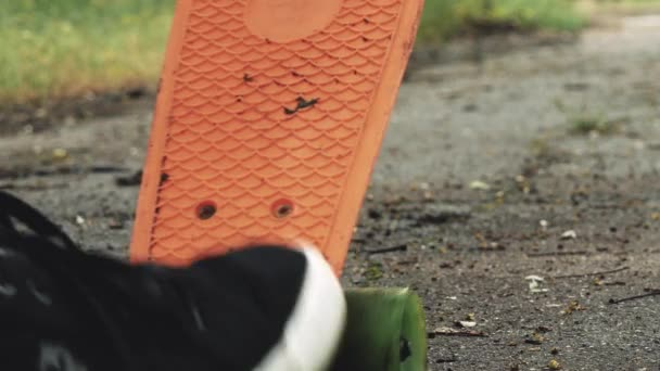 Nahaufnahme der Männer Beine starten Fahrt an Bord im Sommerpark. Skater Junge reiten auf Skateboard in Park im Freien. Orange Skate Fuß tragen Schuhe, Skate Board Deck.