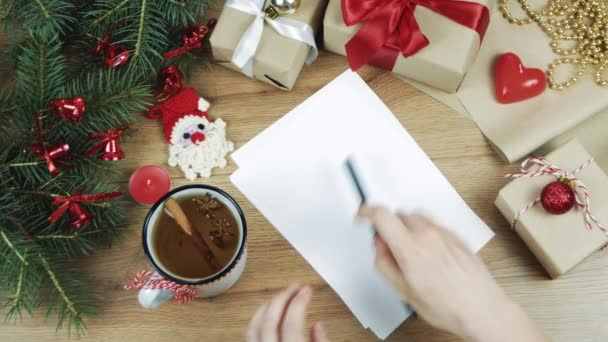 Female hand writing a wish list to Santa on wooden table with gifts, wrapping paper, red Christmas decorations. Xmas and Happy New Year composition. Flat lay, top view