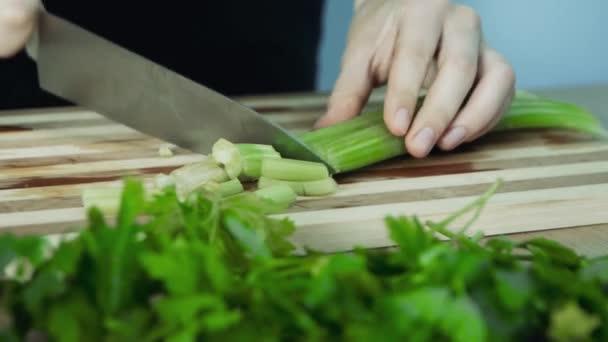 Nůž sekací celer v kuchyni na dřevěné řezné ploše. Šéfkuchař, který vaří celer v kuchyni. Celer pro řezání rukou nůž na sekání dřevěných lepenky.