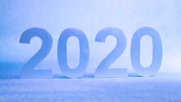 Silver numbers of 2020 on a blue background in the light of a garland, close-up, New Year 2020.