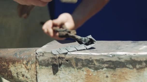 Blacksmith vyrábí plechovou rostlinu. Kladivo. Forge. Close-up. Horký kov. Železa. Zpomaleně.