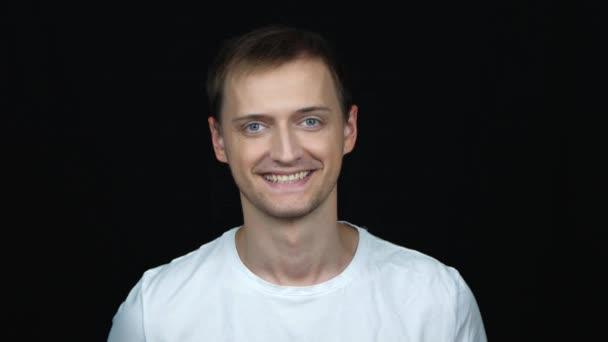 portré elégedett magabiztos kaukázusi ember keres a kamera mosolyogva bólogat pozitívan át fekete háttér. Az érzelmek fogalma