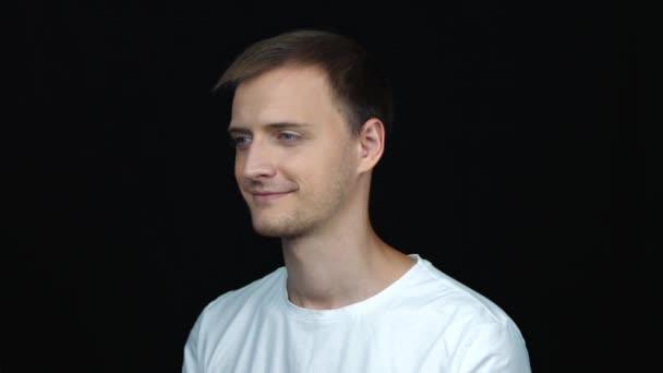 Zavřít profilový pohled na šťastného mladého kavkazského blonďaté muže s úsměvem. Portrét muže na černém pozadí.