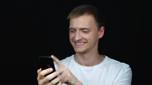 Smiling and laughing young caucasian man in white t-shirt using smartphone over black background. Close up portrait.