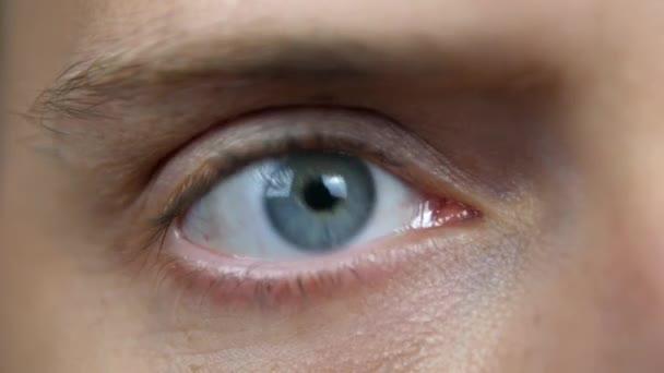 Makroaufnahme eines blauen männlichen Auges. liest der junge Mann schnell den auftauchenden Text. das Konzept der Medien, verwirrter und verängstigter Mensch.