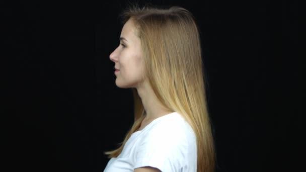 Zavřít profilové zobrazení šťastné mladé kavkazské blondýny s úsměvem. Portrét ženy na černém pozadí.