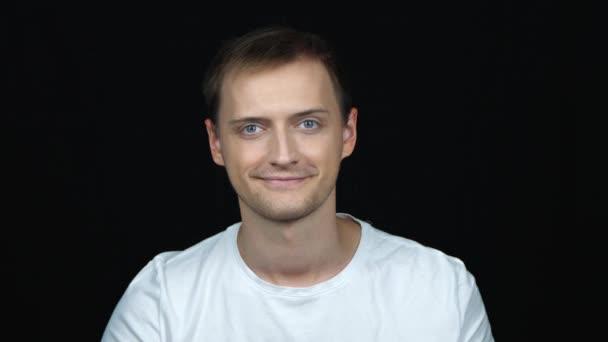 Portrét mladého Kavkazana na černém pozadí. Muž ukazuje znamení podobný a mrknutí. Vypadá přímo na kameru. Na tváři jsou hravé emoce. Pojetí emocí.