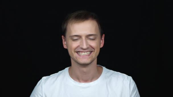 portrét radostně sebevědomého kavkazského muže, který se díval na kameru s úsměvem na černém pozadí. Pojetí emocí