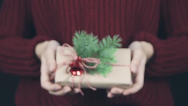 Ženské ruce držící zabalené papírovou krabici s červeným provazem a lukem, ozdobu smrkových větví a vánočního červeného zvonku. Malý dárek v rukou žen. Osoba, která předkládá.