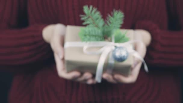 Női kéz tartó becsomagolt kézműves papír ajándékdoboz fehér szalag és íj, dekoráció Luc ág. A női kezek kicsiny jelene. Ajándékot adó személy. Boldog új évet, boldog karácsonyt.