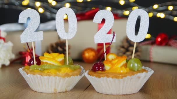 Boldog új évet bogyók cupcakes a 2020 számok bokeh karácsonyi tündér fények háttérben. Cupcakes a számok, mint szimbólum az új év 2020.