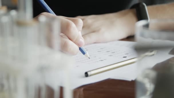 School / university Students hands taking exams, writing examination room with holding pencil on optical form answers paper sheet on desk doing final test in chemistry classroom.