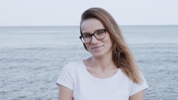 zblízka portrét atraktivní mladé kavkazské ženy, která se dívala na kameru a usmívala se sebevědomě.