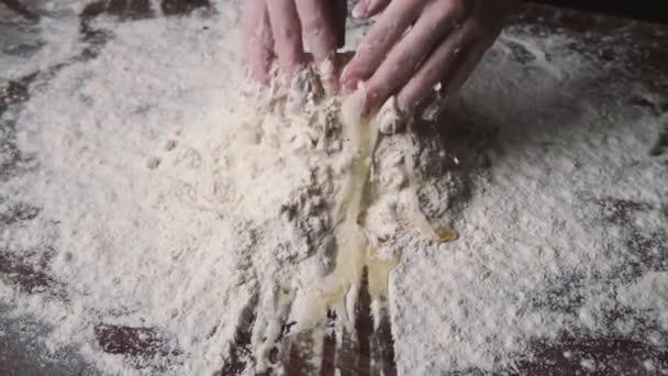 Baker tésztát gyúrt lisztben az asztalon. A liszt tojással és gyúró tésztával való összekeverésének folyamata.