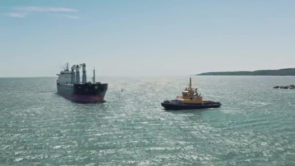 A sárga vontatóhajóról készült légi felvétel egy nagy teherhajóra megy, hogy elvigye a kikötőbe. A teherhajó uszály és vontatóhajó a kikötő kikötőjében találkozik egymással. Légitekintés.