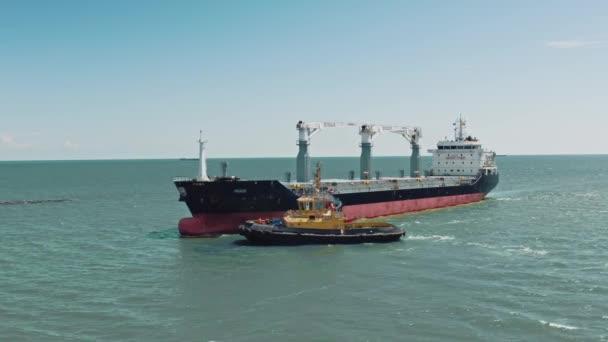 Sárga vontatóhajó által vezetett teherszállító tartályhajó légi felvételei a logisztikai kereskedelmi kikötőbe. Vontatóhajó szállít egy nagy hajót a kikötőbe..