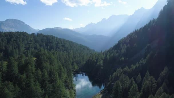 pohybující se vpřed k borovicovým lesům lesní jezero a horské údolí se slunečními erupcemi v letních dnech.Evropa Itálie Alpy venkovní zelená příroda krajina hory divoký vzdušný establishment.