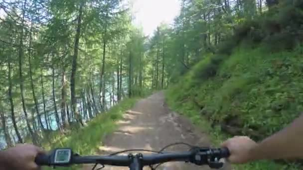 POV man riding e-bike along lake.Mtb action cyclist exploring trail path near mountain forest woods.Electrical bike active people sport travel vacation in Europe Italy Alps outdoors in summer.4k video